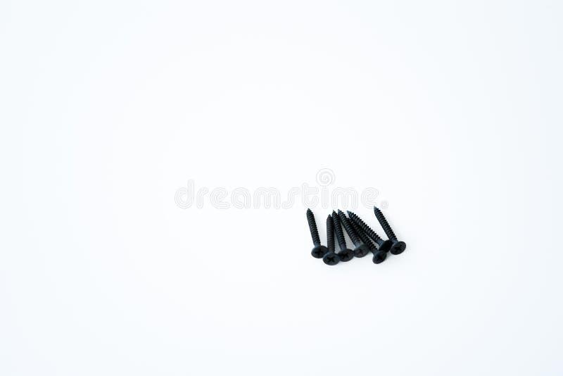 Parafusos pretos dos parafusos debatida dos mesmos tamanhos isolados no fundo branco imagem de stock
