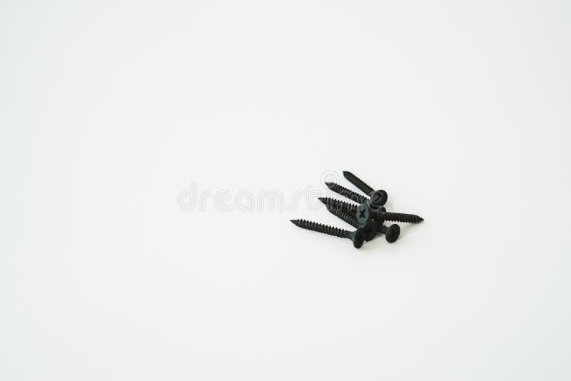 Parafusos pretos dos parafusos debatida dos mesmos tamanhos isolados no fundo branco imagens de stock