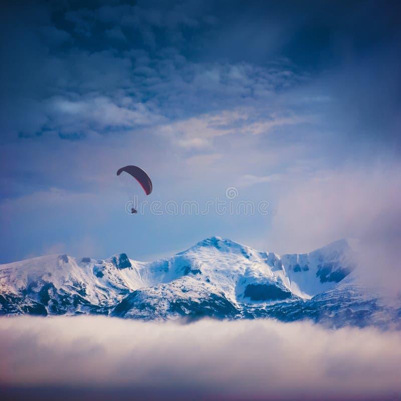 Download Paraglide επάνω από τις χιονοσκεπείς αιχμές Στοκ Εικόνες - εικόνα από κίνδυνος, ολίσθηση: 62718276