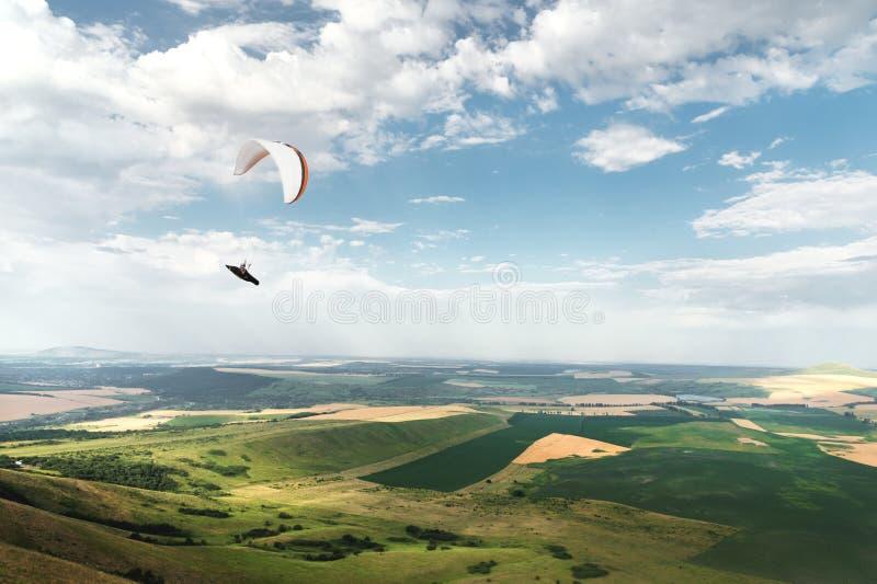 Paraglide arancio bianco con un aliante in un bozzolo contro lo sfondo dei campi del cielo e delle nuvole paragliding fotografia stock libera da diritti