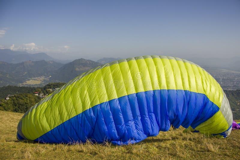 Paraglider żółty błękitny spadochron wzrasta w powietrze przed latać od strony wzgórze przeciw tłu zieleń fotografia royalty free