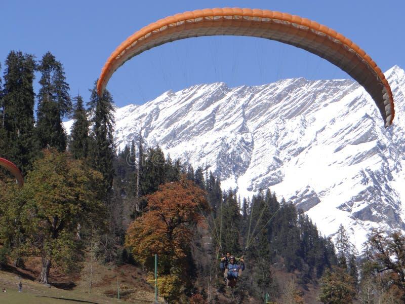 Paraglider cieszy się jego przejażdżkę w śnieg zakrywającym pasmie górskim w INDIA obrazy royalty free