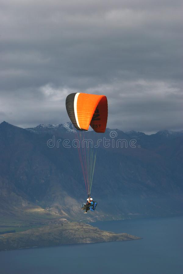 Paraglider em tandem que voa sobre o lago no dia nebuloso fotos de stock