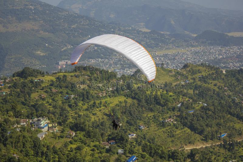 Paraglider flies over the green mountains and the village in the valley. The paraglider flies over the green mountains and the village in the valley stock image