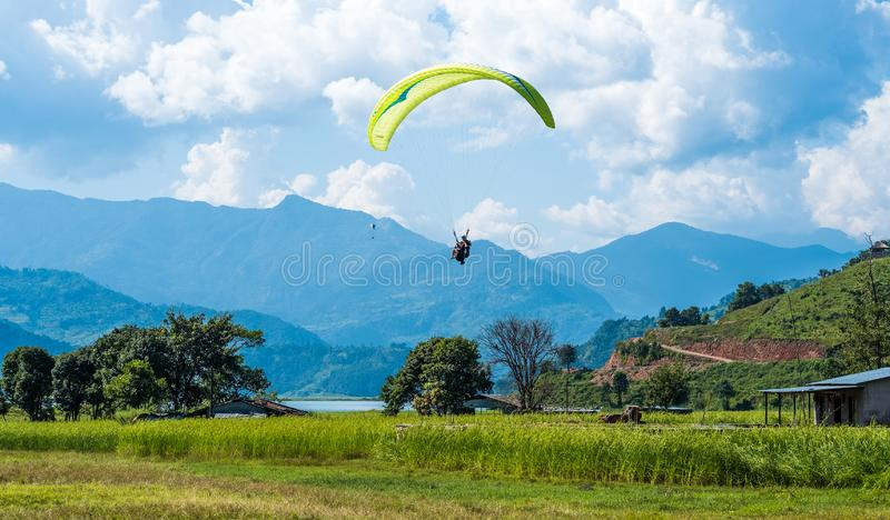 Paraglider flies over a meadow, Pokhara, Nepal stock images