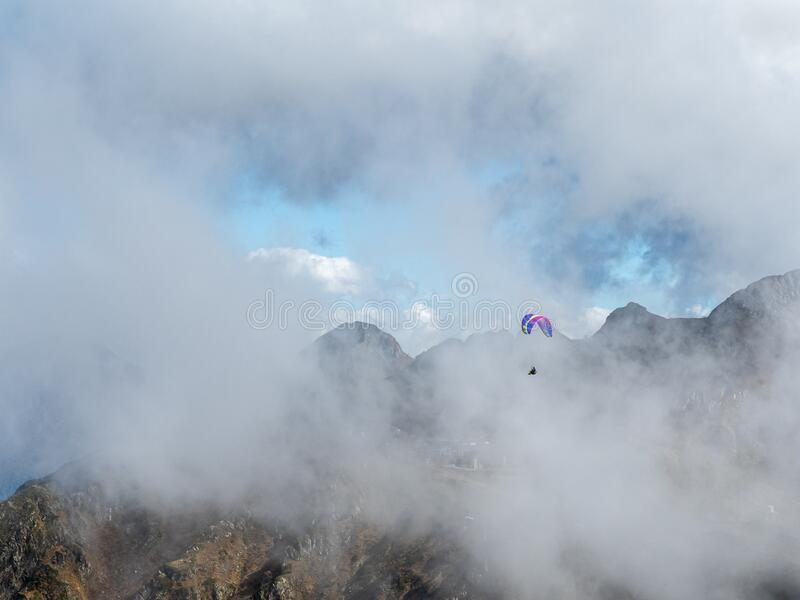 Paraglider flies over the mountains through clouds and fog stock image