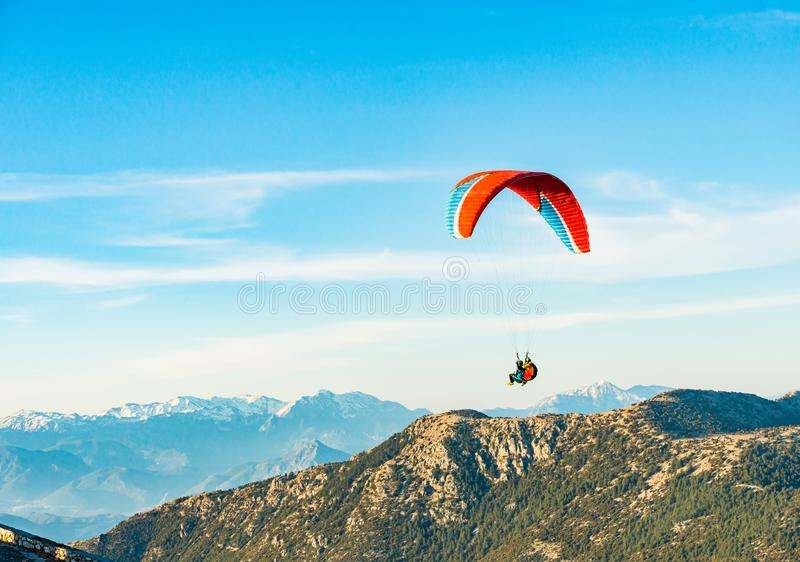 Paraglider floating in the air with blue sky and mountains on background in Turkey. Bright paraglider floating in the air with blue sky, green hills and stock photos