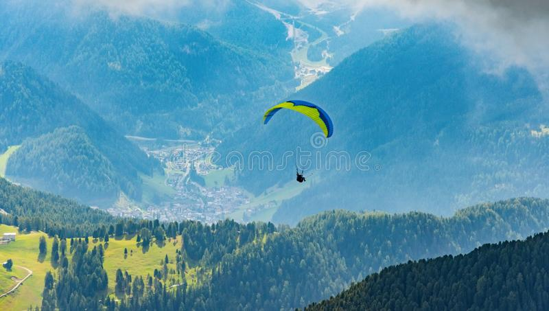 Paraglider flying above mountains, Dolomites, Italy stock image