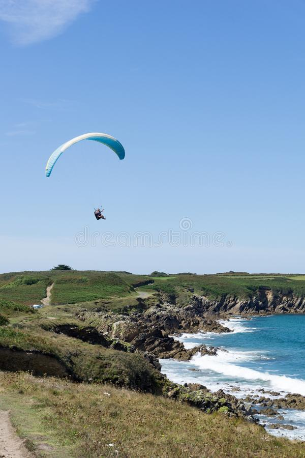 Paraglider flying above a picturesque sandy beach on te rocky coast of Brittany stock images