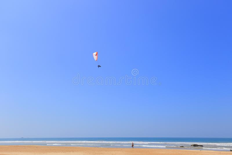 Paraglider flying along the beach stock photography