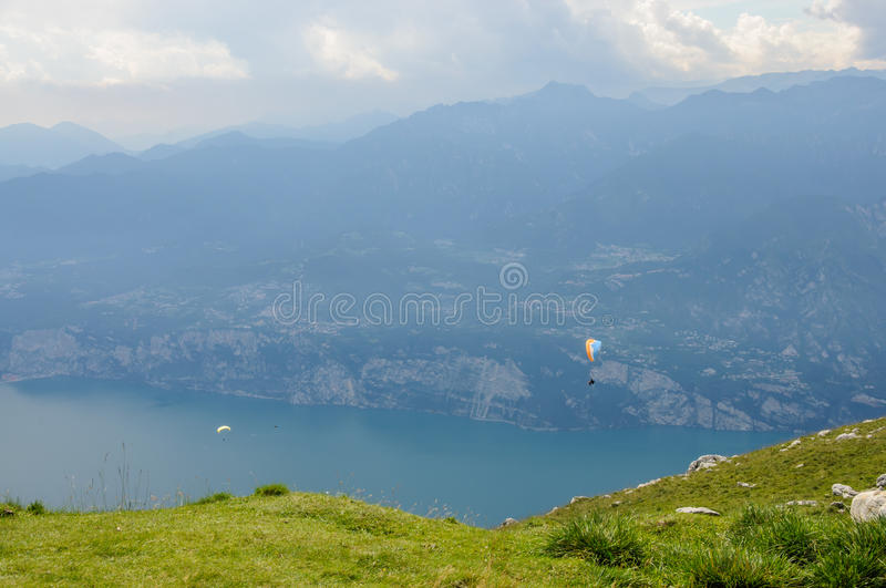 Paraglider is flying in front of mountain landscape of Alps - Mo. Paraglider is flying in front of mountain landscape of Italian Alps - Monte Baldo stock photos