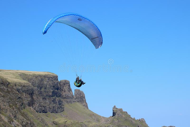 Paraglider flying off Scottish mountain royalty free stock image