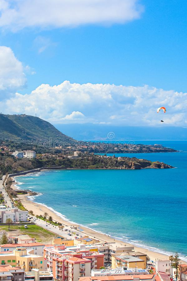Paraglider flying over the amazing sea landscape by coastal Cefalu in Italian Sicily. Captured on a vertical photography. With hills behind the beautiful bay royalty free stock image