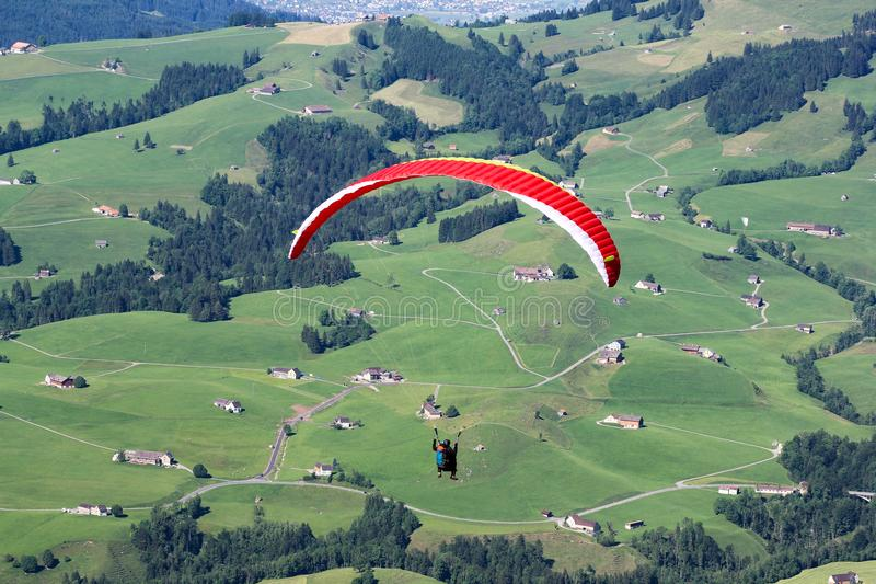 Paraglider flying over the field in teh Alps stock photo