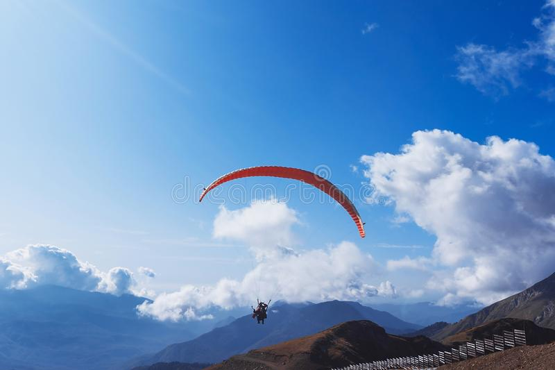 Paraglider flying over the mountains on a bright summer day. Paragliding sport concept. Copy space stock photography