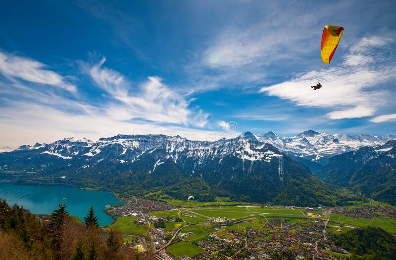 Paraglider flying over mountains at sunny summer day, Interlaken, Swiss Alps. Paraglider flying over mountains and Interlaken valley against picturesque sky at stock photo