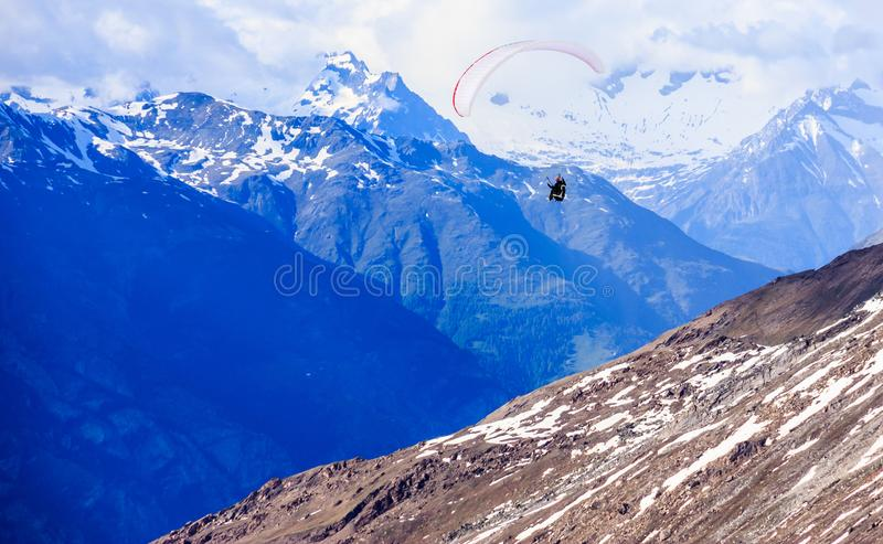 Paraglider flying over mountains in the summer day sky, Paragliding recreation sport leisure activities. Swiss Alps in Zermatt stock photos
