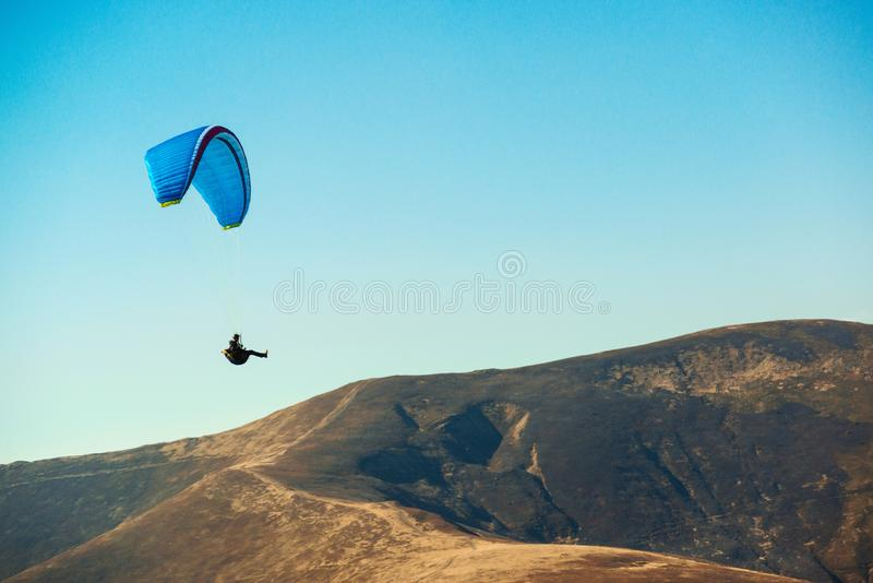 Paraglider flying over mountains in sunny day. Freedom concept. Soaring flight moment. Paragliding in the sky. Extreme sport. stock photos