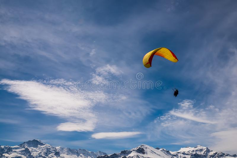 Paraglider flying over mountains at sunny summer day, Swiss Alps royalty free stock photography