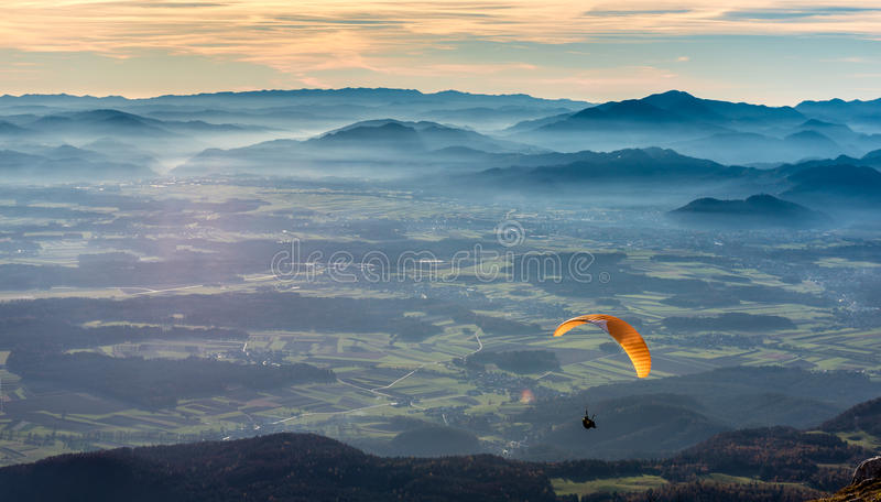 Paraglider is flying in the valley. Paragliding from the mountain with perfect view royalty free stock image