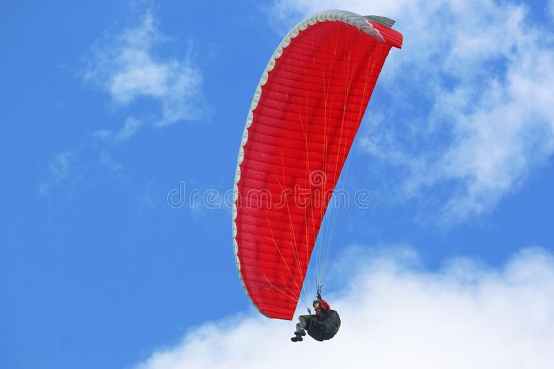 Red paraglider in a blue sky. Paraglider flying wing in a blue sky stock images