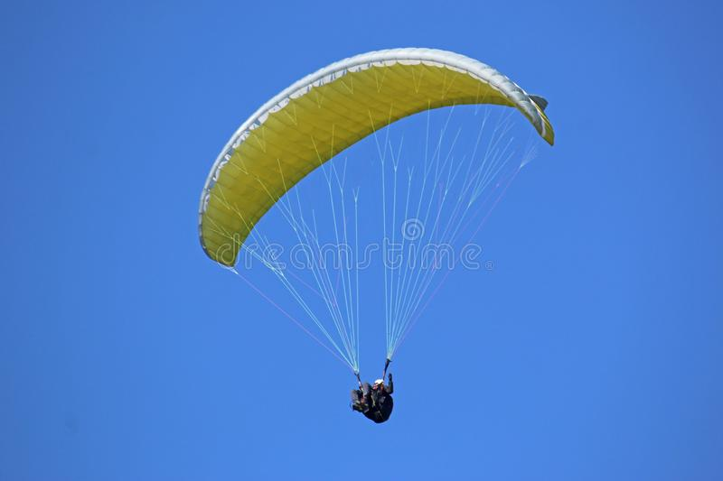 Paraglider flying yellow wing stock photo