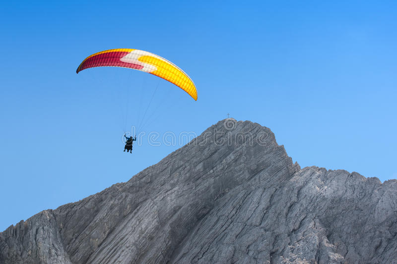 Paraglider free soaring in cloudless sky over dolomites Alpine m. Paraglider free soaring at a great height in cloudless sky over dolomites Alps peak mount stock image