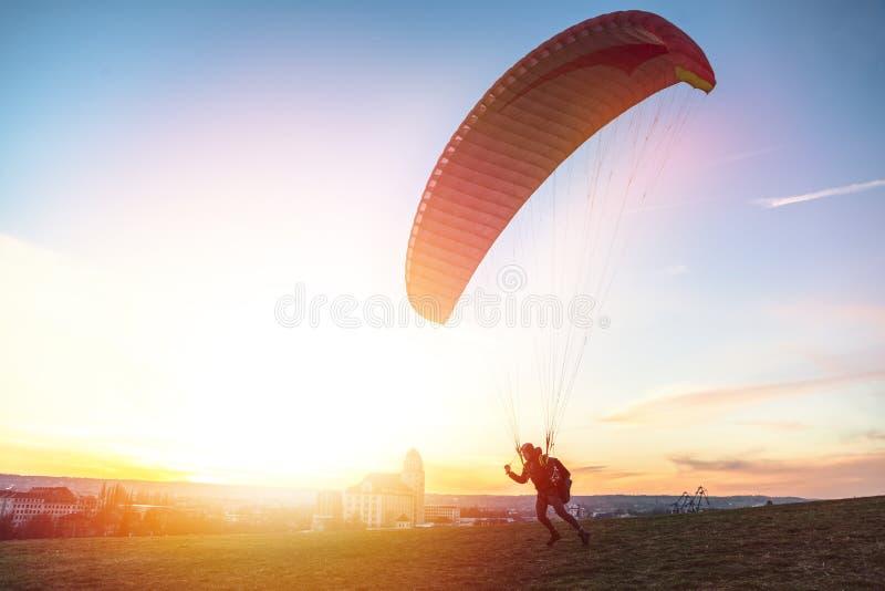 Paraglider getoff ziemia z wiatrem przeciw zmierzchowi fotografia stock