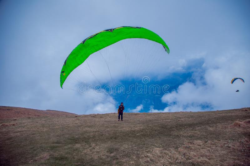 Paraglider with a green parachute is on the mountain, going to take off. To the right can be seen soaring a paraglidera. Paraglider with a green parachute is on royalty free stock image