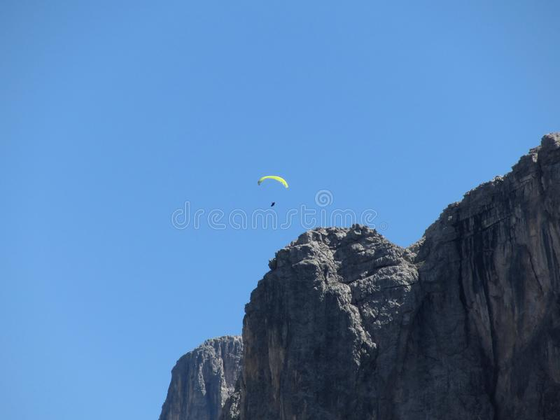 Paraglider with his yellow parachute flying near high italian mountains . Dolomites, Italy royalty free stock photo