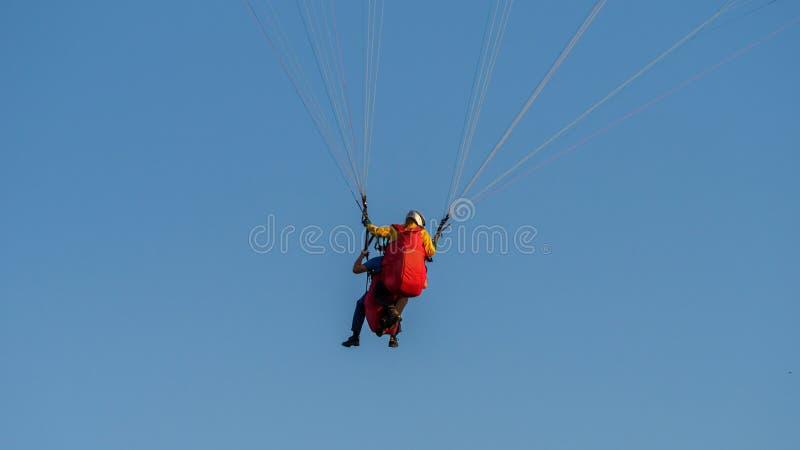 Paraglider med passanger som flyger i den blåa himlen arkivbilder