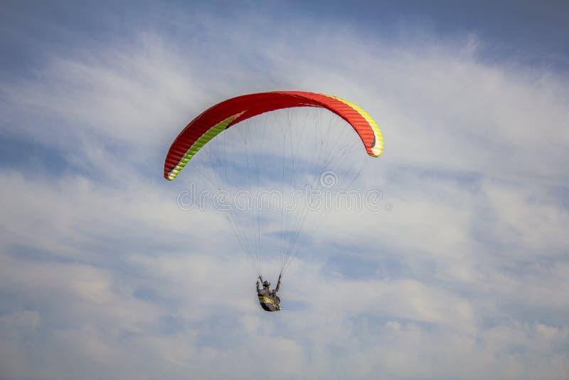 Paraglider na czerwieni z kolorów żółtych lampasów paraglider lata w niebieskim niebie z białymi chmurami obrazy stock
