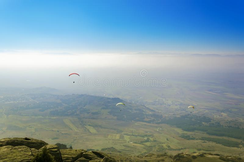 Paraglider pilot pov of people paragliding over the mountain royalty free stock image