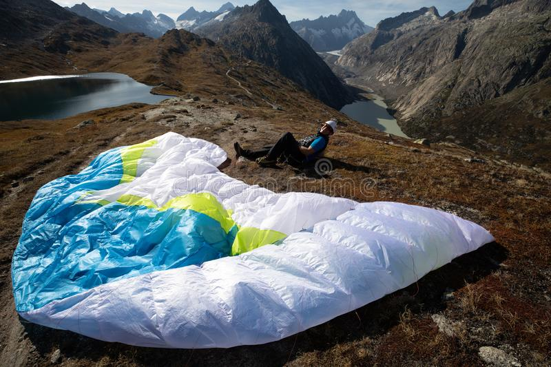 Paraglider Pilot sits with his paraglider on the ground and recovers after ground handling. Location: Grimsel, Switzerland stock images