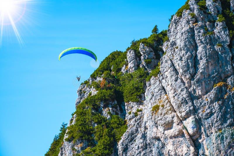 Paraglider que voa perigosamente perto dos picos de montanha em um dia ensolarado do outono imagens de stock royalty free