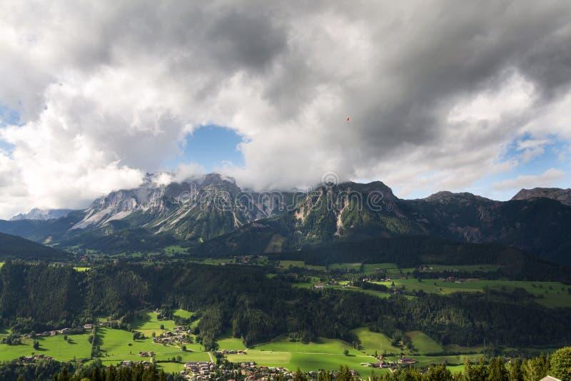 Paraglider que voa sobre Schladming, fundo das montanhas de Dachstein, cumes, Áustria foto de stock