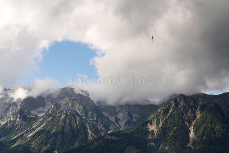 Paraglider que voa sobre Schladming, fundo das montanhas de Dachstein, cumes, Áustria imagens de stock