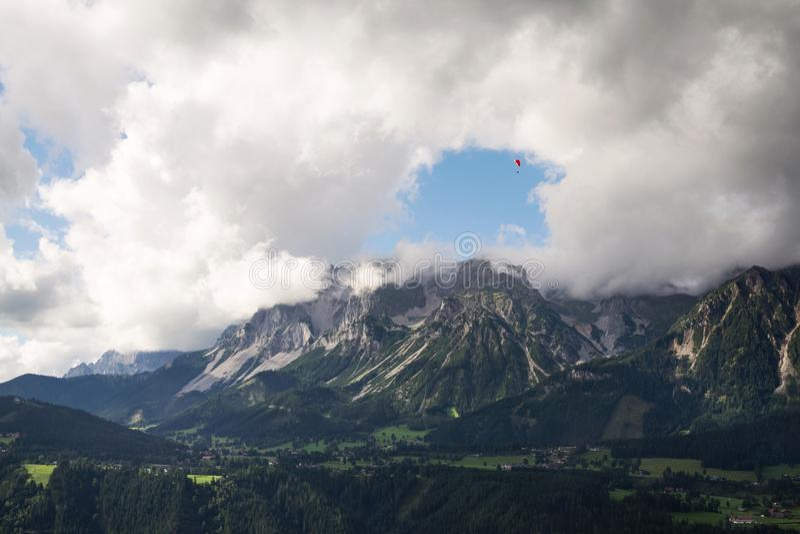 Paraglider que voa sobre Schladming, fundo das montanhas de Dachstein, cumes, Áustria imagens de stock royalty free