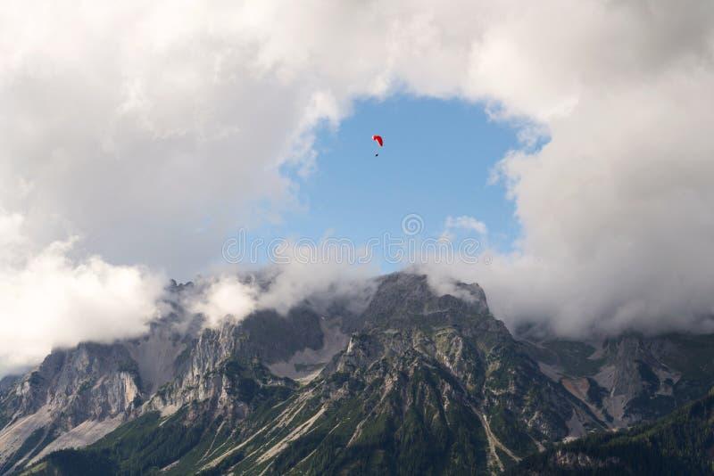 Paraglider que voa sobre Schladming, fundo das montanhas de Dachstein, cumes, Áustria foto de stock royalty free