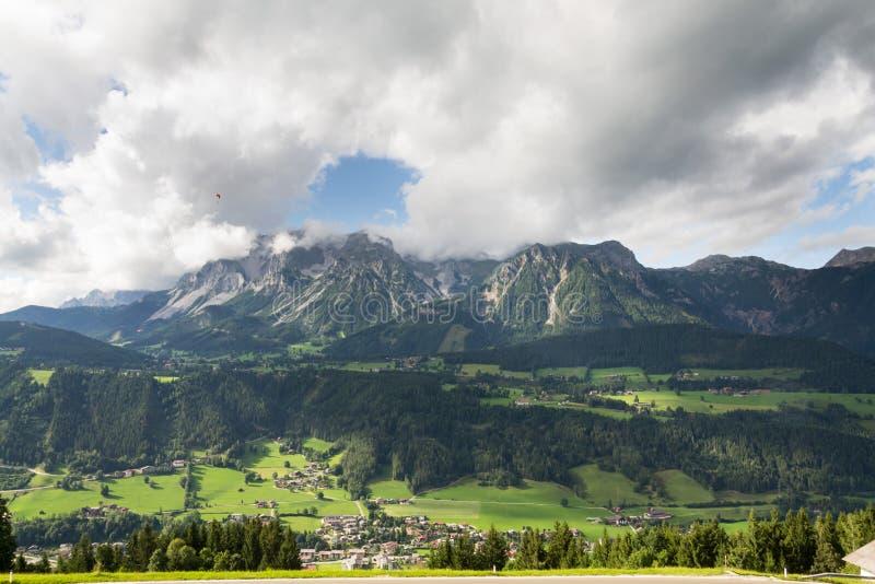 Paraglider que voa sobre Schladming, fundo das montanhas de Dachstein, cumes, Áustria fotos de stock