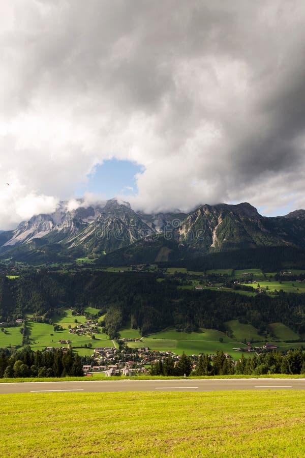 Paraglider que voa sobre Schladming, fundo das montanhas de Dachstein, cumes, Áustria fotografia de stock