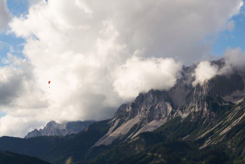 Paraglider que voa sobre Schladming, fundo das montanhas de Dachstein, cumes, Áustria imagem de stock royalty free