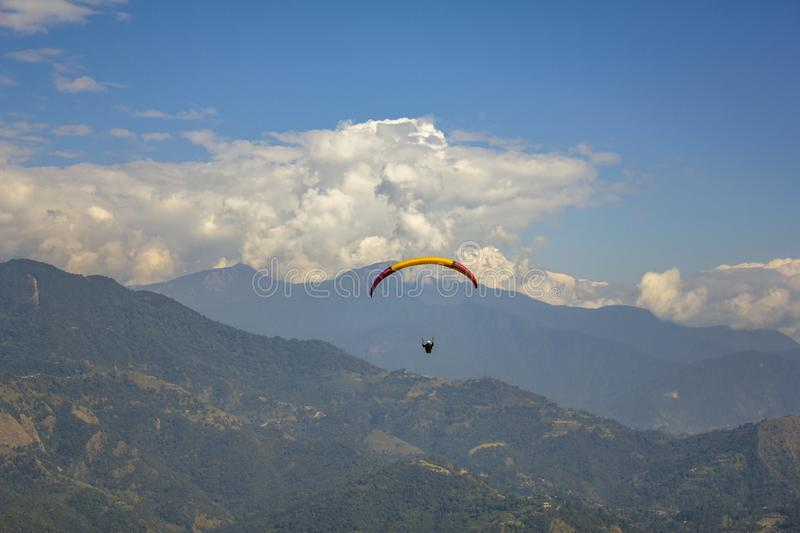 Paraglider on a red-yellow parachute flies against a background of green mountains and white clouds in the blue sky, aerial view royalty free stock photos