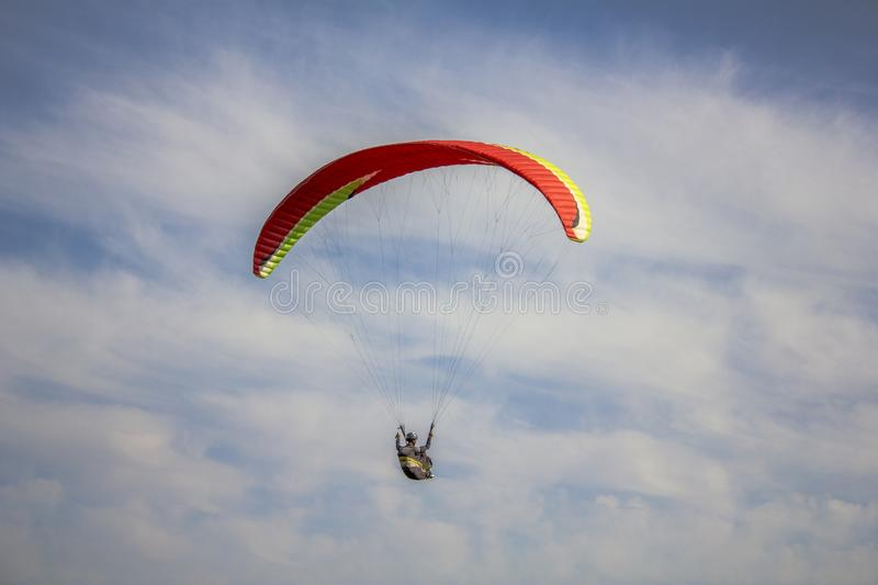 Paraglider on a red with yellow stripes paraglider flies in a blue sky with white clouds stock images