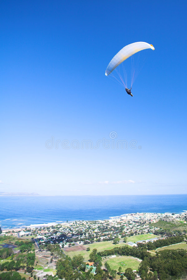Paraglider ridge soaring next. Paraglider launching from the ridge with an orange and white canopy and the sun from behind. The paraglider is standing out royalty free stock image
