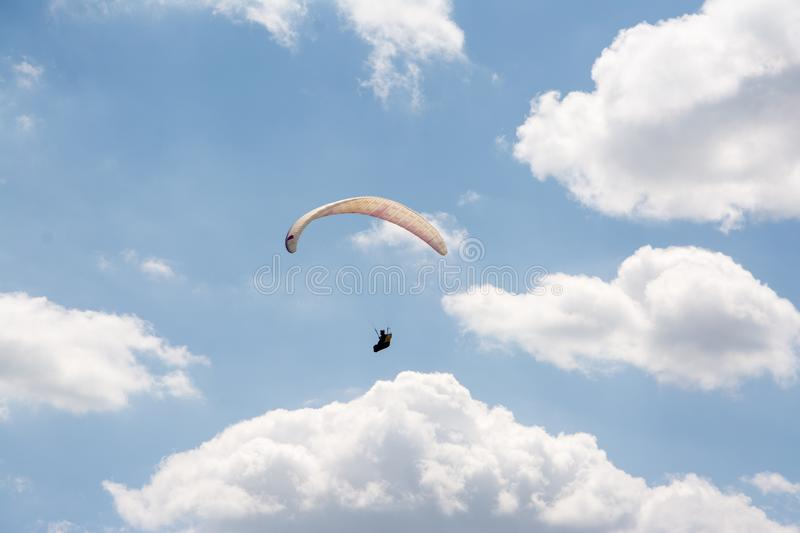 Paraglider seen from below alone in the sky stock images