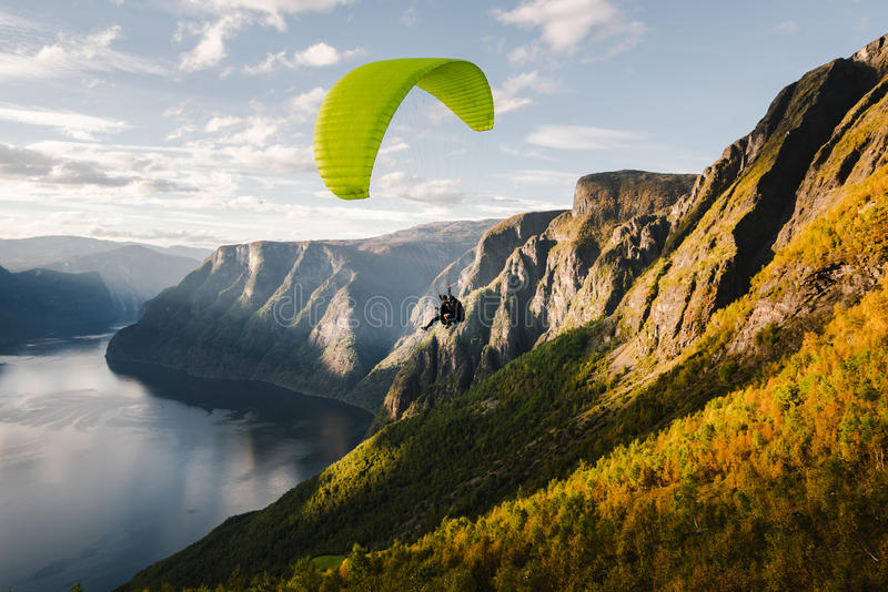 Paraglider silhouette flying over Aurlandfjord, Norway.  stock photo