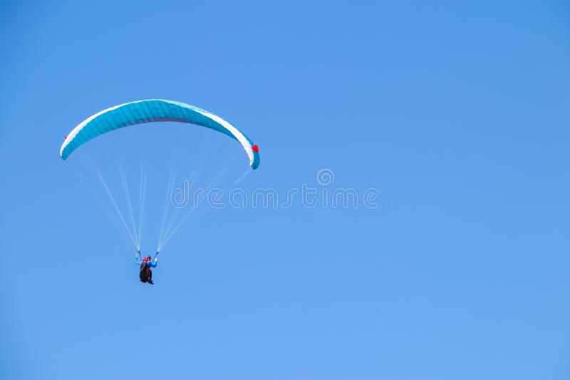 Paraglider soaring in the blue sky. Paraglider soaring in the blue sky stock photo