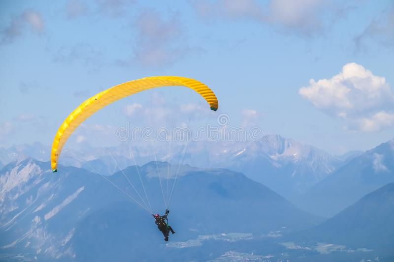 Paraglider soaring in the blue sky over the beautiful mountains. Paraglider soaring in the blue sky over the beautiful mountains stock photography