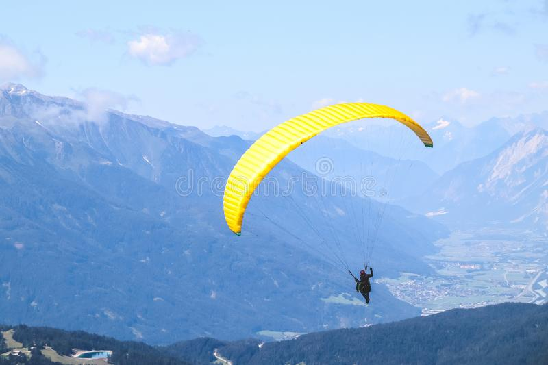 Paraglider soaring in the blue sky over the beautiful mountains. Paraglider soaring in the blue sky over the beautiful mountains stock photos
